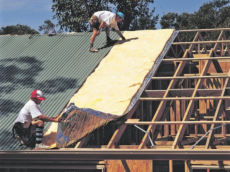 Two men installing insulation on a roof