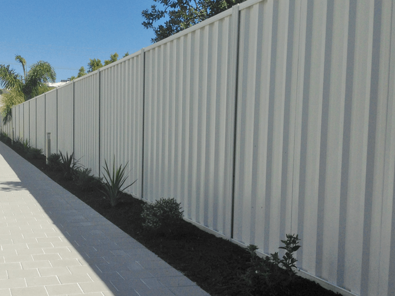 Installed driveway fence made from Trimclad Colourbond fence in Surfmist.